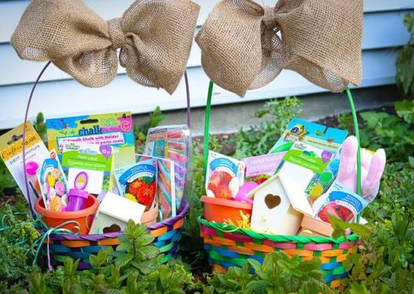 2 easter baskets with burlap bows tied on them and garden themed fillers
