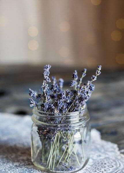 a mason jar on a table cloth with lavender inside