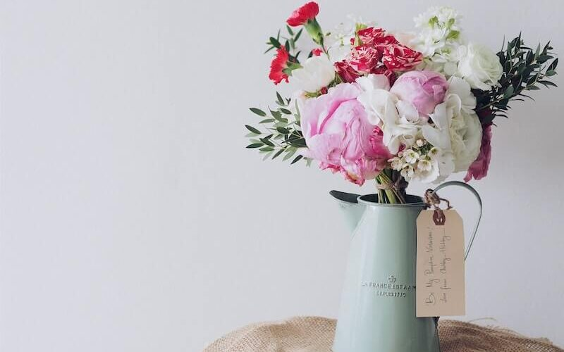 a steel water can with a bouquet of flowers in it and. and a tag around water can