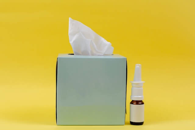 a tissue box and allergy medication