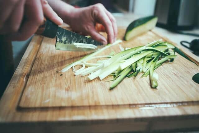 a hand slicing up a cucumber on a wood cutting board
