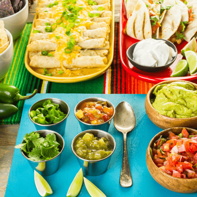 a table filled of taco toppings, tacos and dips