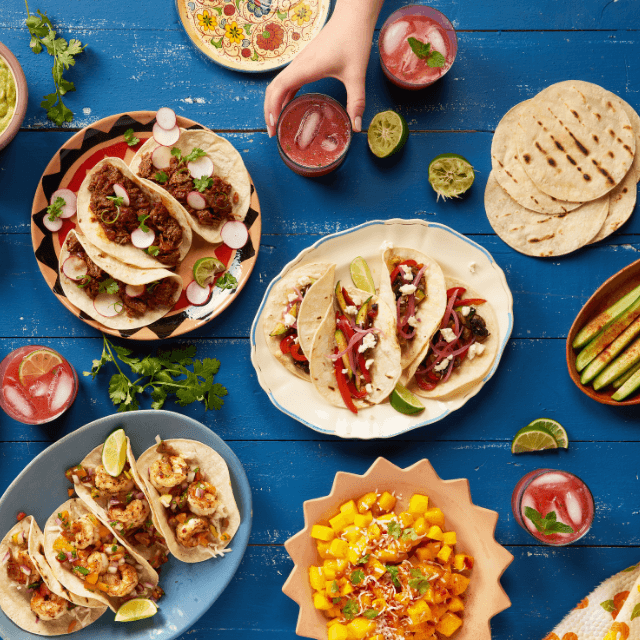 a mix of different types of tacos on a blue table and a hand grabbing a drink