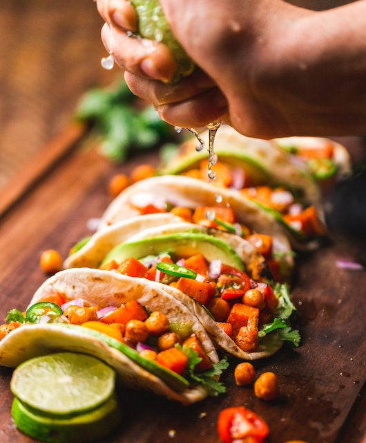 tacos filled with taco toppings and a had squeezing lime on top