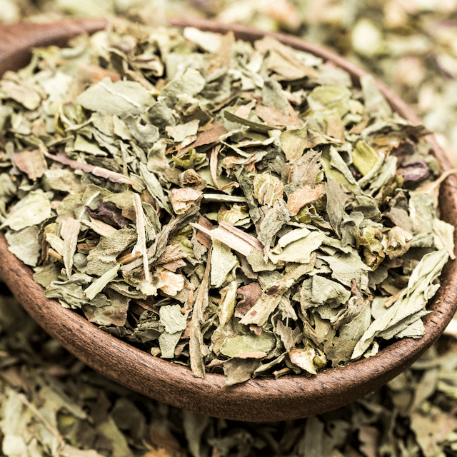 dry basil in a wooden spoon
